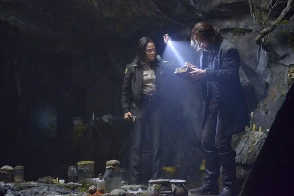 Ichabod and Abbie examine George Washington's bible in a cave on Sleepy Hollow