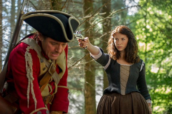 Claire holds a gun on a redcoat on Outlander
