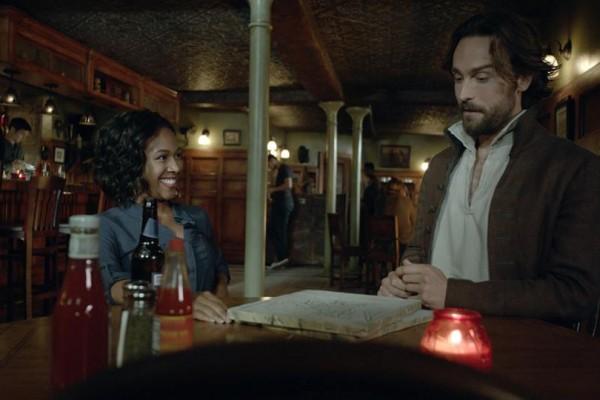 "Ichabod (Tom Mison) and Abbie (Nicole Beharie) share drinks in the Sleepy Hollow, season premiere, ""I, Witness."""